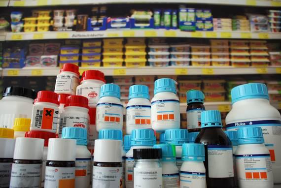 Chemiekalien-Behälter vor einem Supermarktregal
